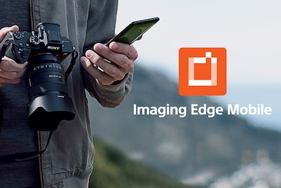 Homme tenant un α1 et un smartphone avec logo de l'application Imaging Edge Mobile