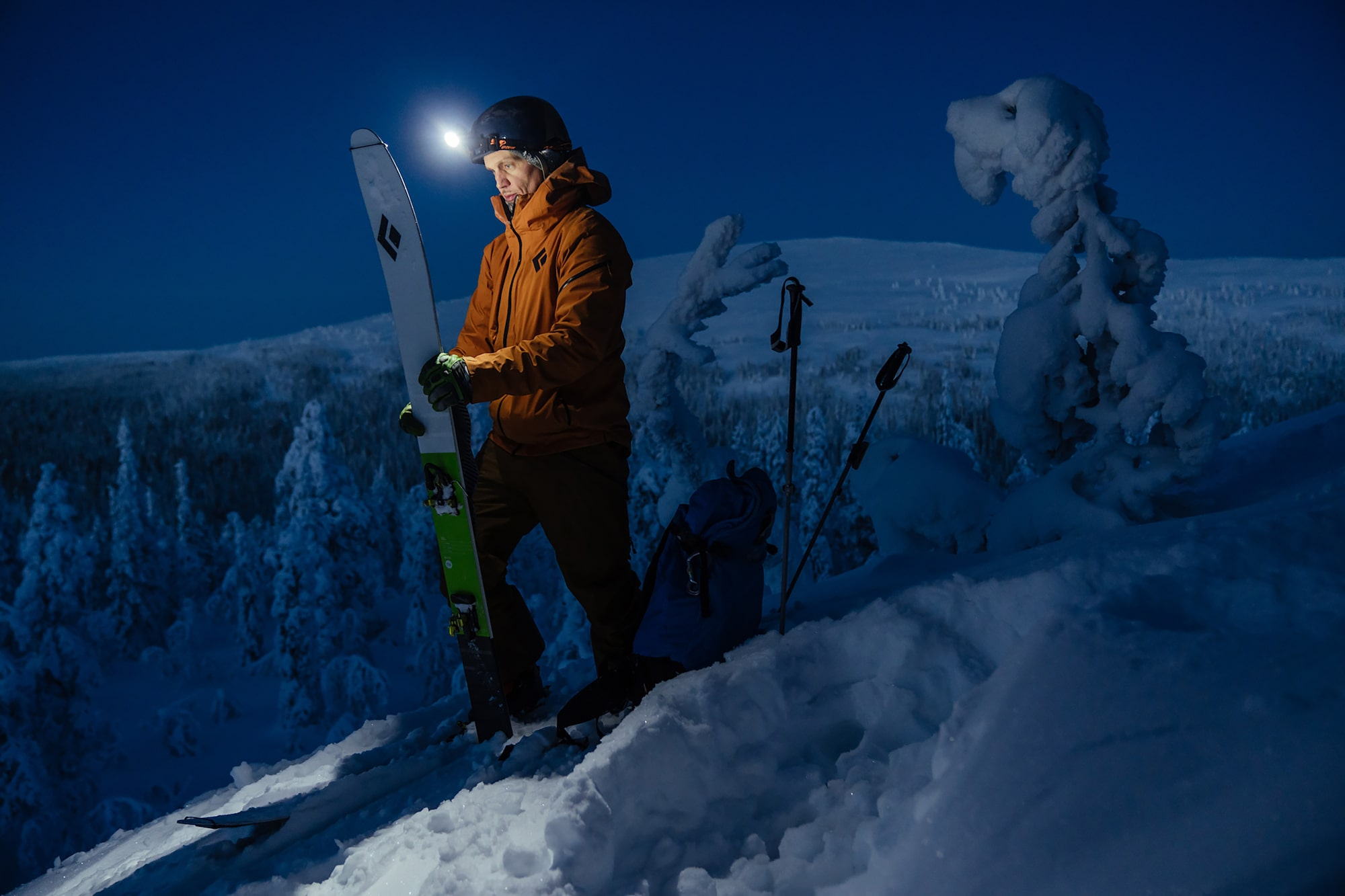 jaakko posti sony alpha 9 skieur inspectant ses skis à l'aide d'une lampe frontale
